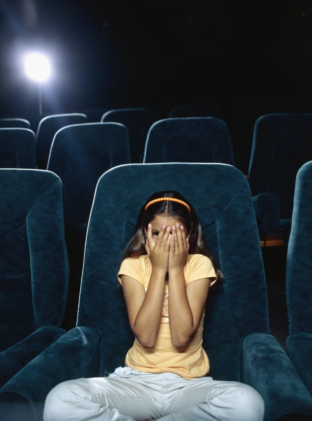 Girl covering her face with her hands in a movie theatre