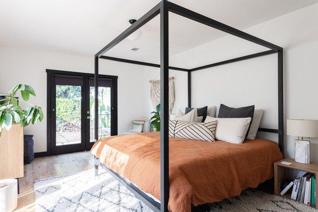 Minimal boho bedroom with black bed frame and organic color palette