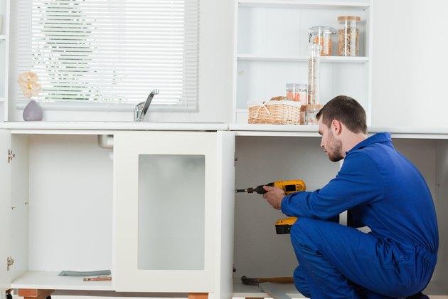 Good looking handyman fixing a door
