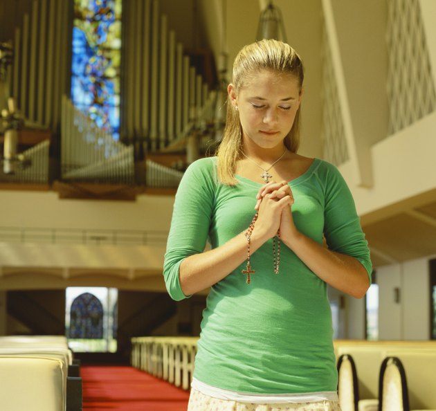 close-up of a teenage girl praying in a church