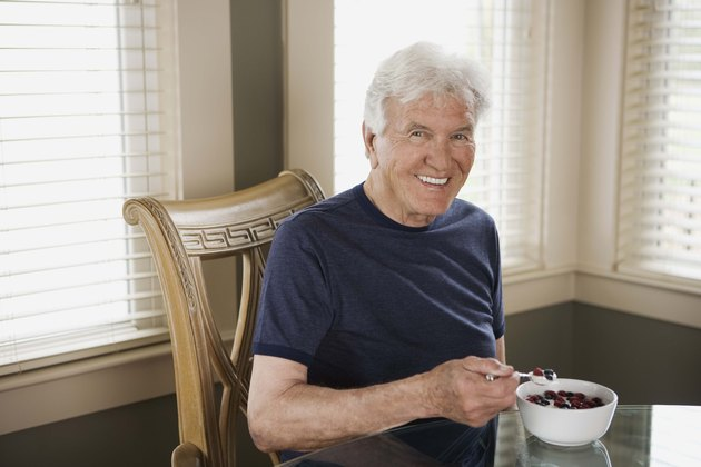 Man with bowl of berries and cream