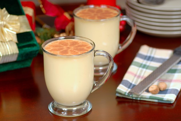 Two glasses of rich eggnog in a holiday table setting