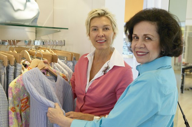 Mature Female Shop Assistant Helping a Senior Woman Choose a Jumper From a Clothes Rail in a Clothes Shop