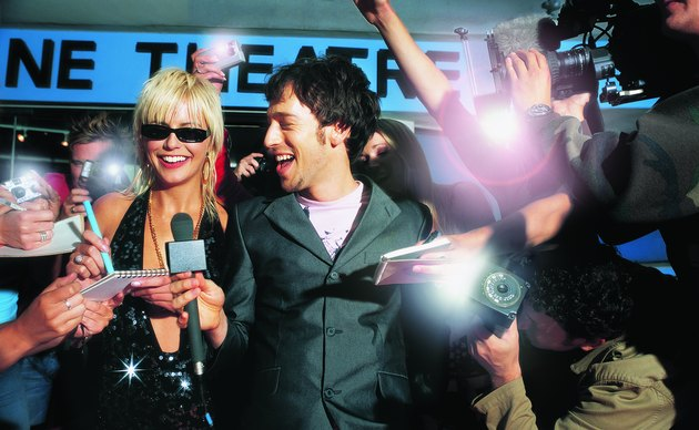 Actress Being Interviewed by a TV Reporter as Her Fans Photograph Her