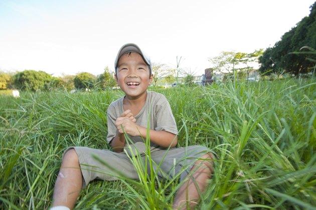 Boy sitting on grass, Japan