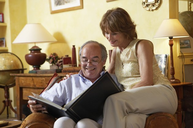 Mature couple sitting on armchair looking at photo album, smiling