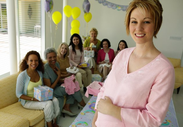 Pregnant woman at baby shower, guests in background, portrait