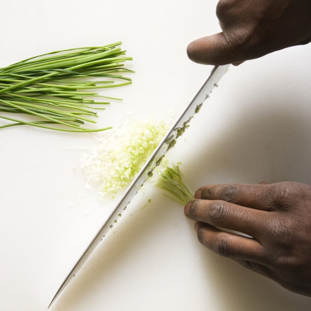 African-American male hands using large kitchen knife to chop fresh chives.