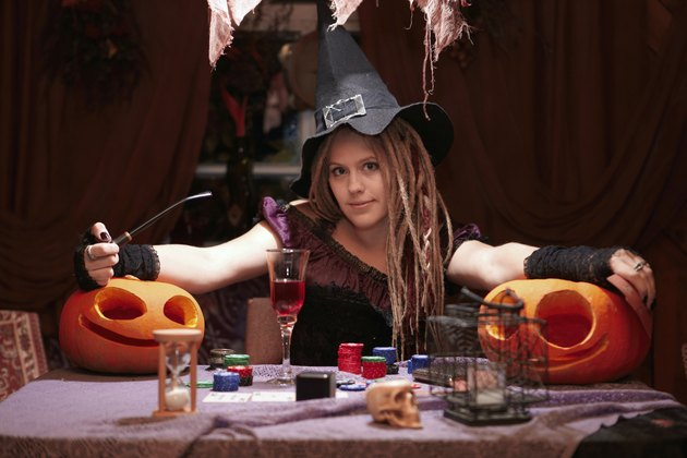 Halloween casino. Witch with smoking pipe and pumpkins.