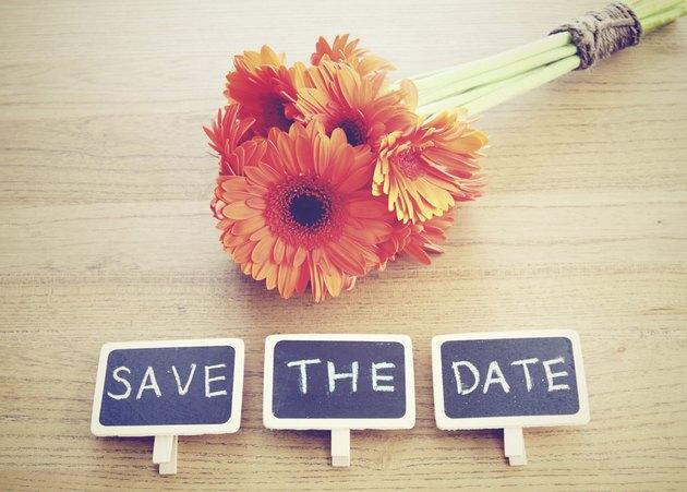 Save the date written on blackboard with flower