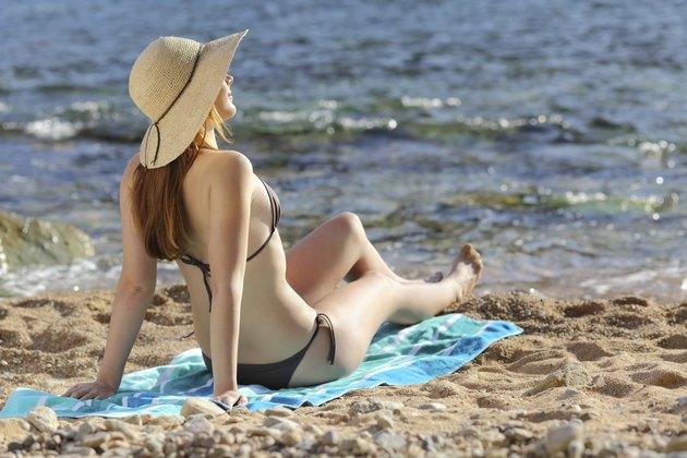 Woman sunbathing on the beach in summer