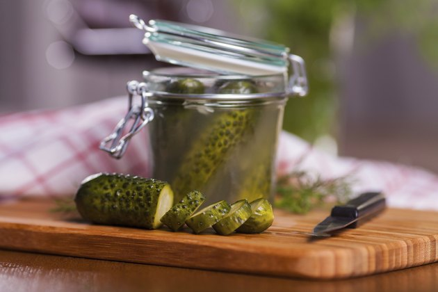 Pickled cucumbers in jar on cutting board