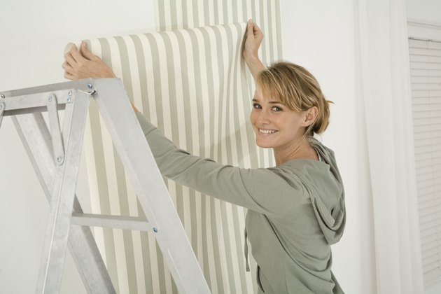 Woman hanging wallpaper
