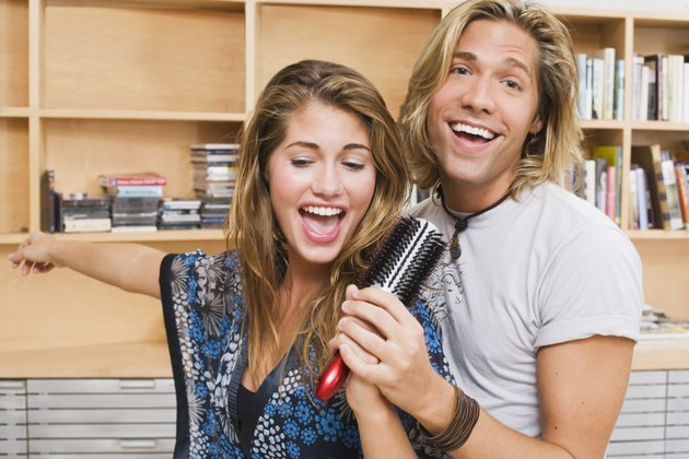 Couple singing into hairbrush