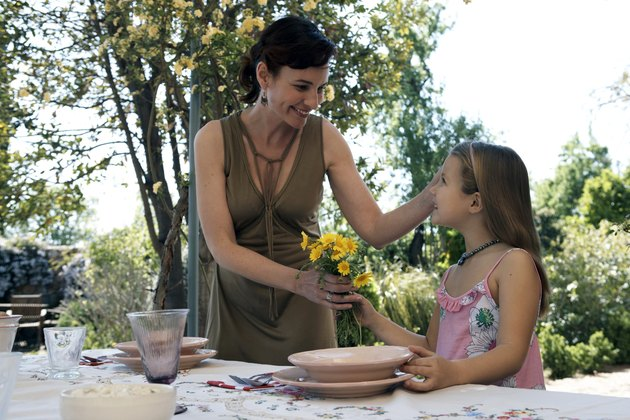 Girl (8-9) giving mother bunch of flowers at dining table