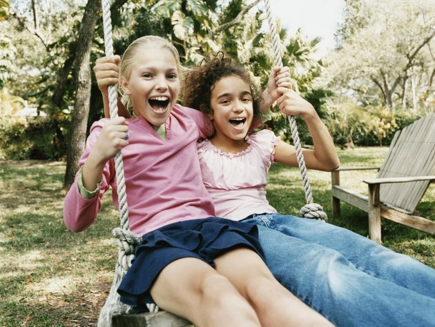 Two Young Girls Sit Side by Side on a Swing in a Garden, Laughing