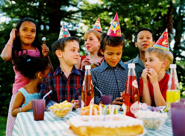 Group of children (4-10) standing in front of a table with cake and snacks celebrating a birthday