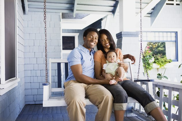Smiling family seated on porch swing