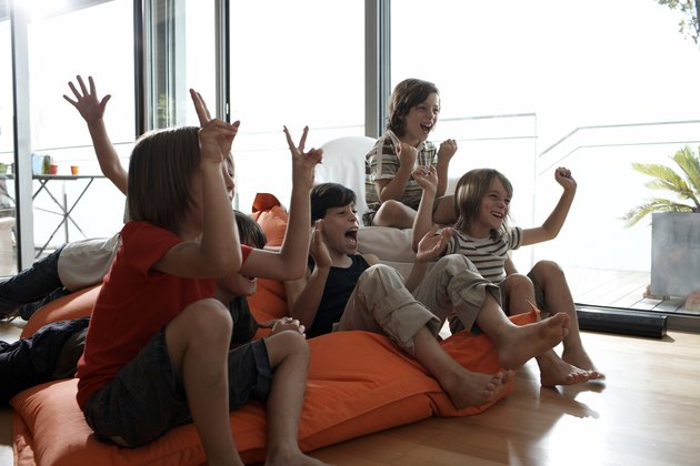 group of boys cheering in front of a television
