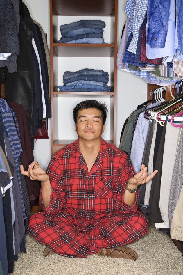 Man in pajamas sitting in yoga position in closet