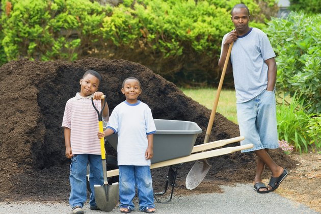 Mid adult man and his two sons holding shovels