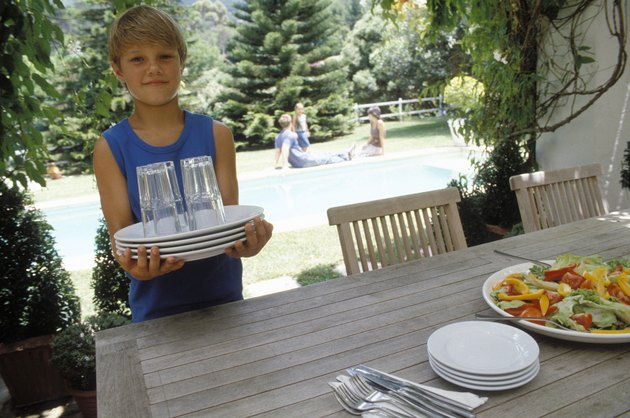 Boy carrying dishes to table
