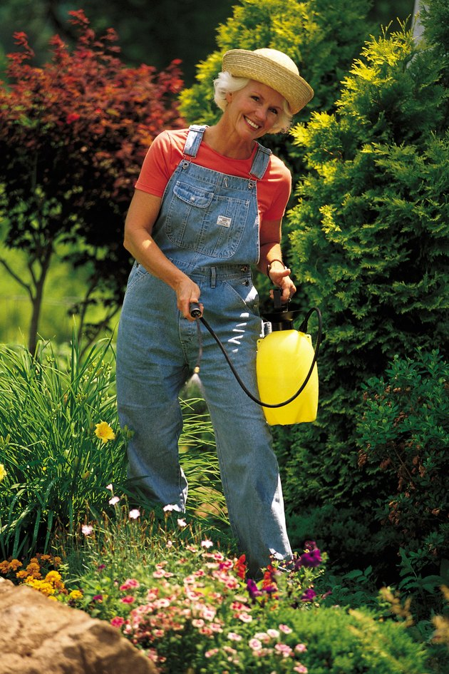 Woman with spray can in garden