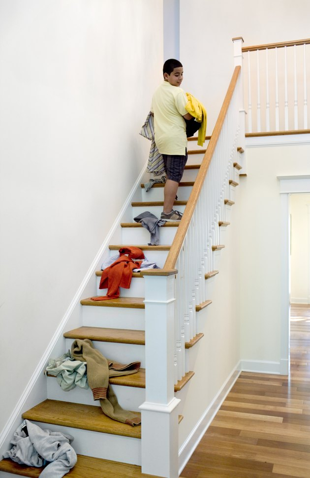 Boy dropping laundry while carrying it upstairs