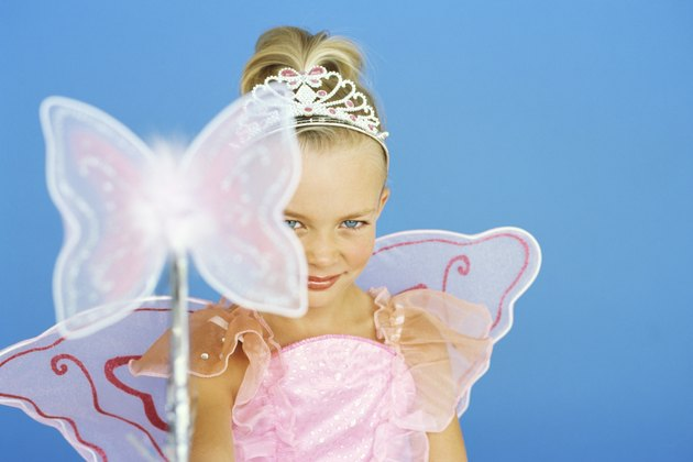 portrait of a girl wearing a fairy costume and holding a magic wand