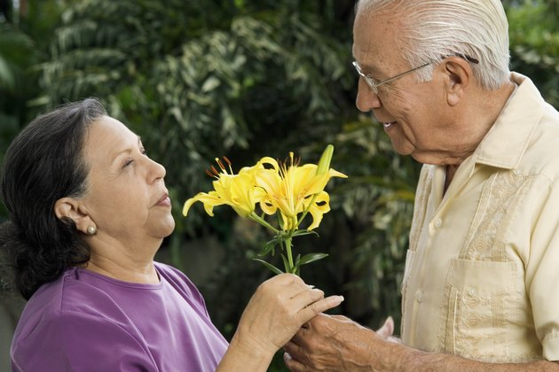 Senior man giving senior woman flowers outdoors, close-up