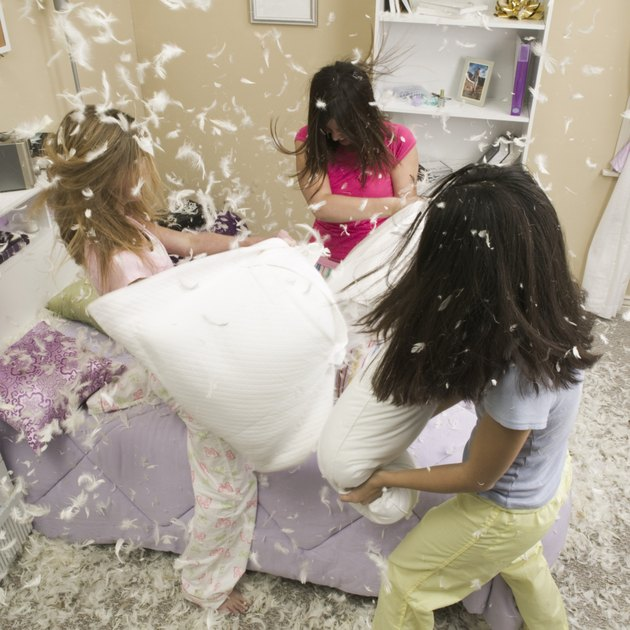 High angle view of three teenage girls having a pillow fight