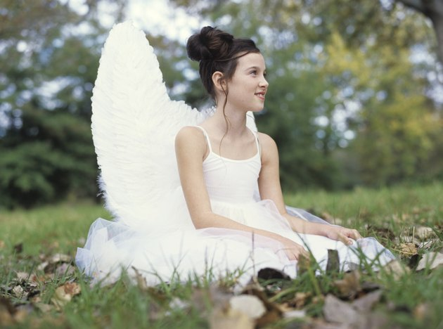 Girl (9-11) sitting on grass wearing angel costume, side view