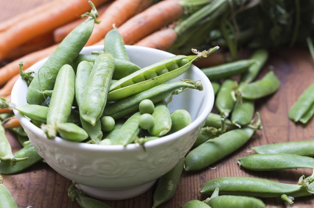 Pea pods in a bowl with carrots