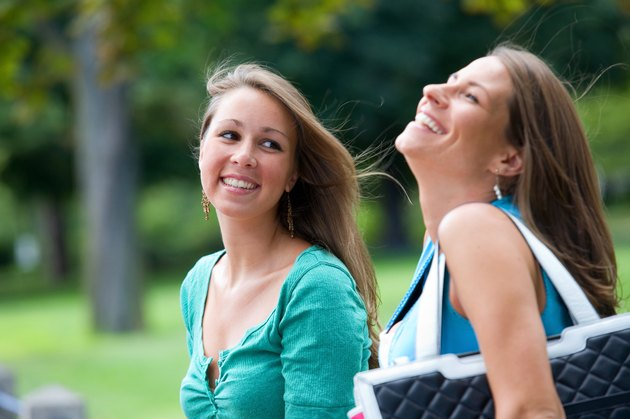 Two smiling teenage girls outdoors at park