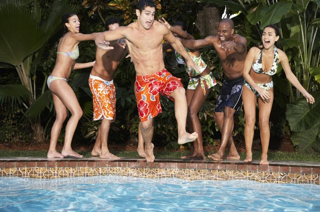 Young Friends Pushing Man in Swimming Pool