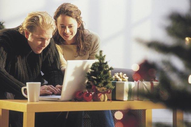 Couple using computer at Christmas