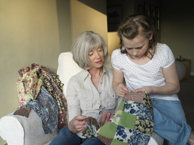 Grandmother and granddaughter (9-11) sewing quilt