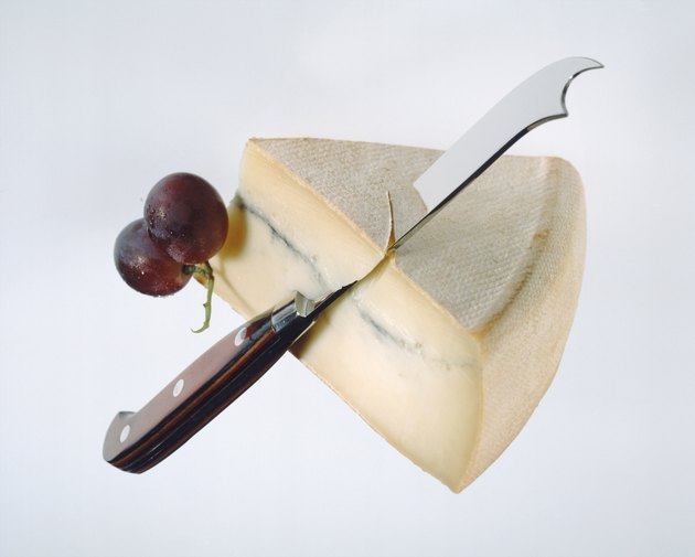 Slice of cheese, grape and knife on white background, close-up