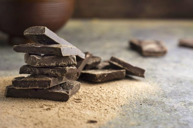 pieces of dark chocolate stacked on grunge background