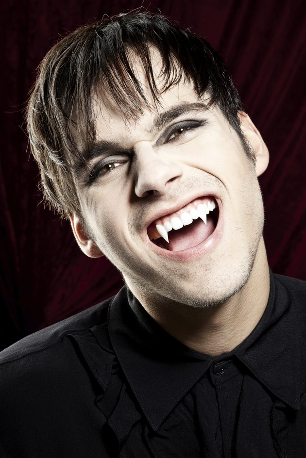 Male vampire laughing dangerously and showing his fangs