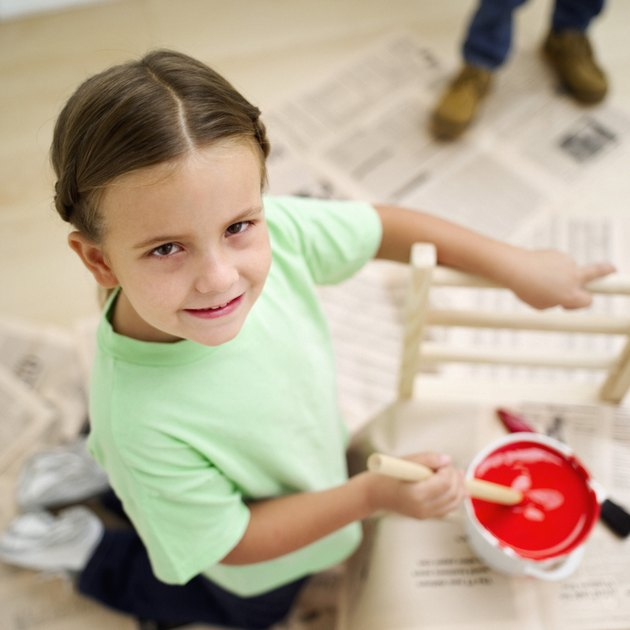 High angle view of a girl stirring a bucket of red paint