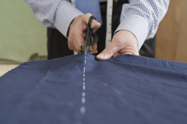 Tailor cutting fabric with scissors