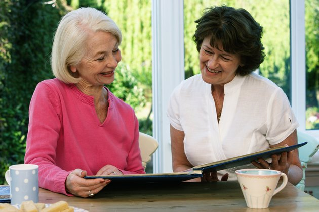 Two senior women sitting at kitchen table looking at album, smiling