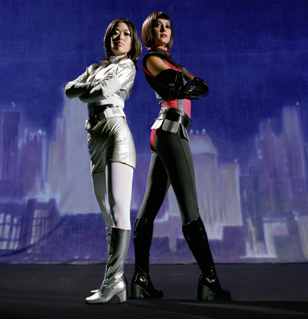 Two women in futuristic costumes, painted skyline in background
