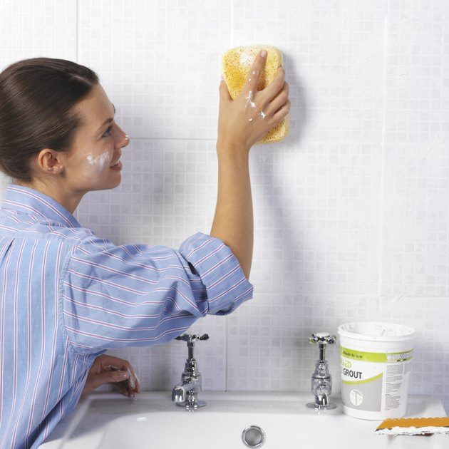 Woman cleaning tile wall in bathroom