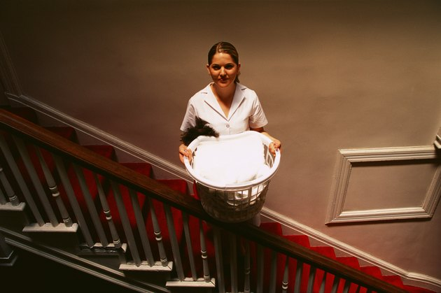 Man standing on staircase with laundry basket