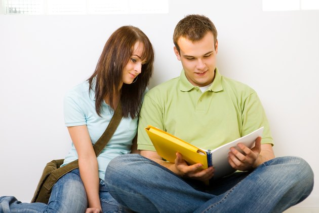 Teenage boy and girl sitting on floor reading together