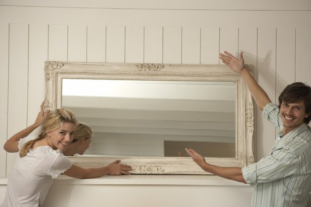 Couple hanging a mirror