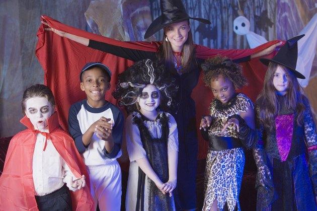 Woman spreading cape around children in Halloween costumes