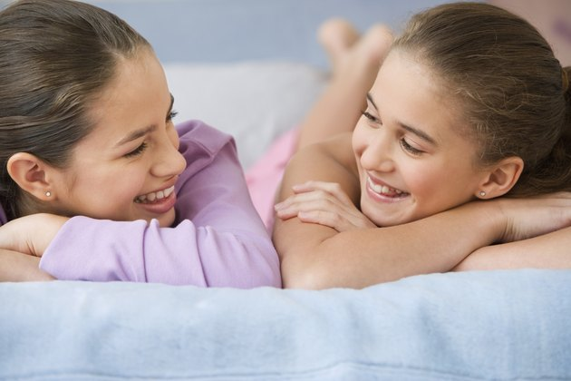 Hispanic sisters smiling at each other on bed